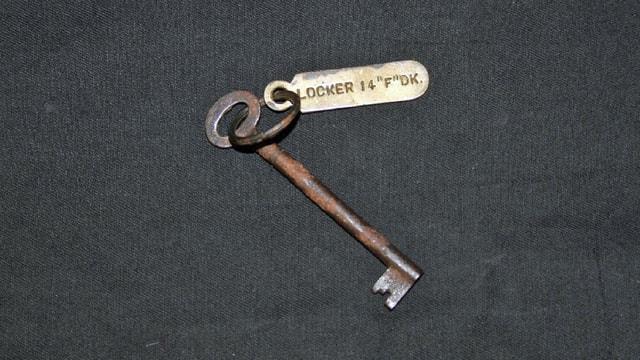 Ein rostiger Schlüssel mit einem Anhänger.