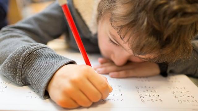 Primarschüler löst Rechnenaufgaben mit dem Bleistift.