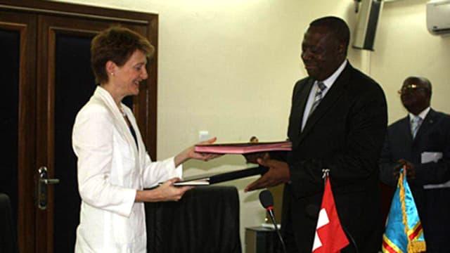 Simonetta Sommaruga und Richard Muyej Mangez mit Dokumenten in den Händen