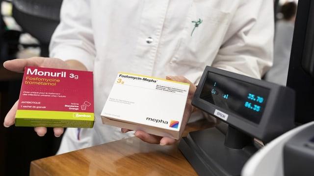 Apotheker präsentiert zwei Medikamente.