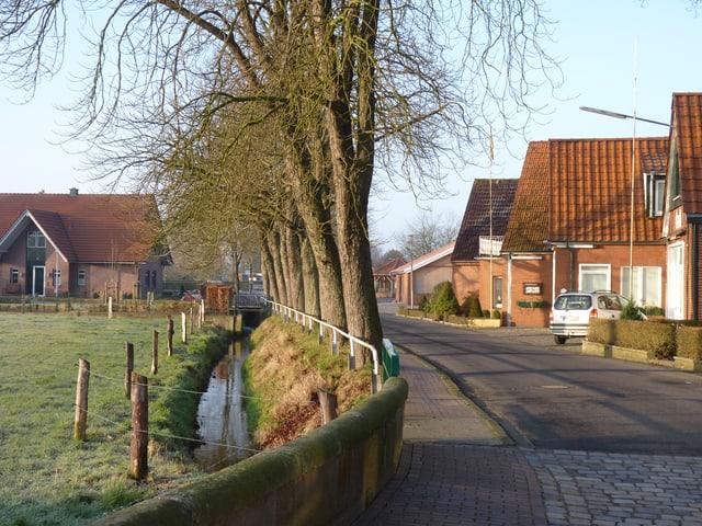 Sicht auf eine Strasse, die durch ein Dorf führt, auf der anderen Seite eine Allee.