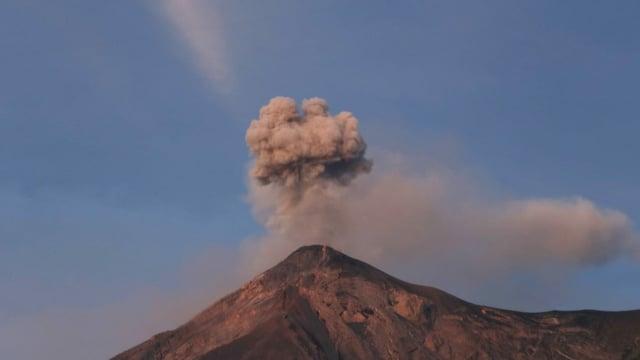 Der Feuervulkan speiht eine Rauchwolke.