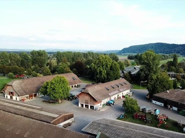 Luftansicht von Witzwil, grosse Gebäude mit Holzdach, landwirtschaftliche Fahrzeuge.
