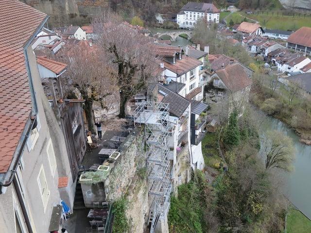 Blick von oben auf Häuser, die am Rand der steilen Felswand stehen. Unten die Saane.