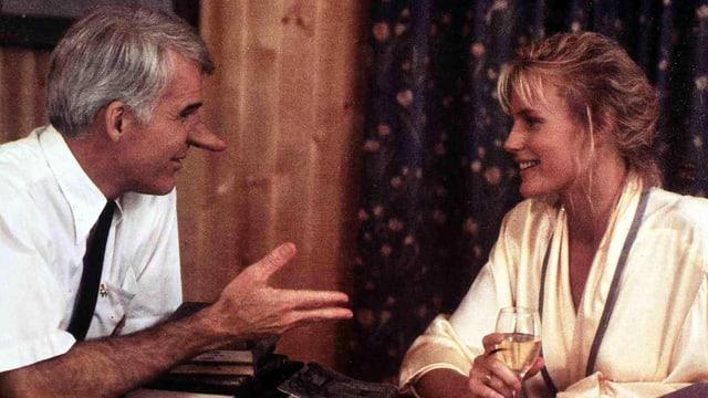 Ein Mann mit einer langen Nase spricht mit einer hübschen Frau