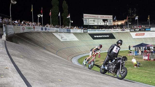 Ein stehender Motoradfahrer gibt das Tempo an, der Radrennfahrer folgt im dicht hinterher.