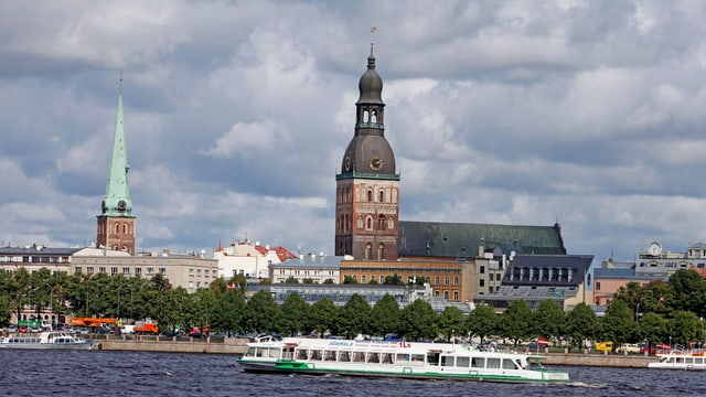 Ein Schiff fährt auf einem Fluss vor einer Kathedrale vorbei.