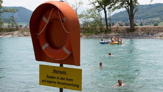 Ein oranger Ständer mit einem Rettungsring im Vordergrund. Dahinter badende Menschen in der Aare.