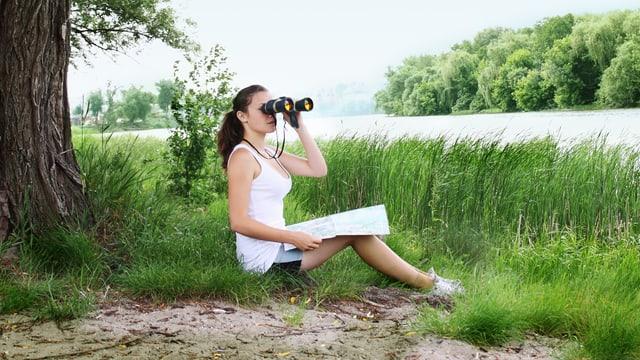 Frau mit Fernglas an einem See
