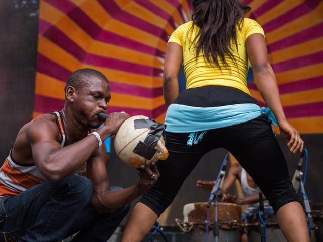 Ein Mann bläst kniend ein aus einer Schiffsboje gebautes Instrument. Daneben tanzt eine Frau, die um die Hüfte ein Tuch gebunden hat.