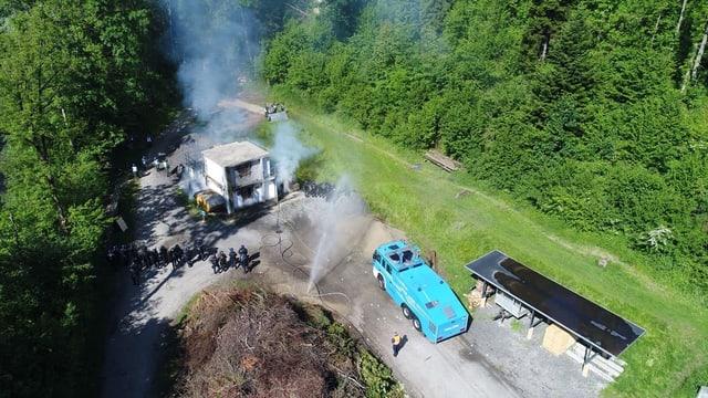 Ein blaues Fahrzeug in der Nähe eines brennenden Gebäudes.