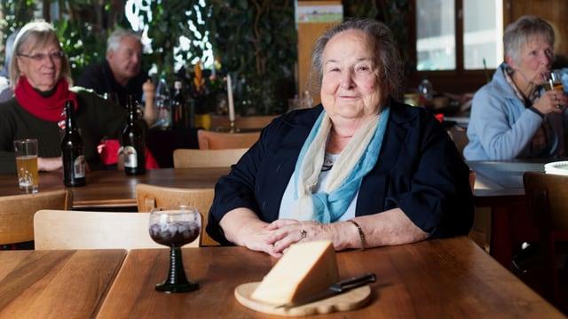 Die Wirtin sitzt am Tisch, vor sich ein Glas und ein Stück Käse.