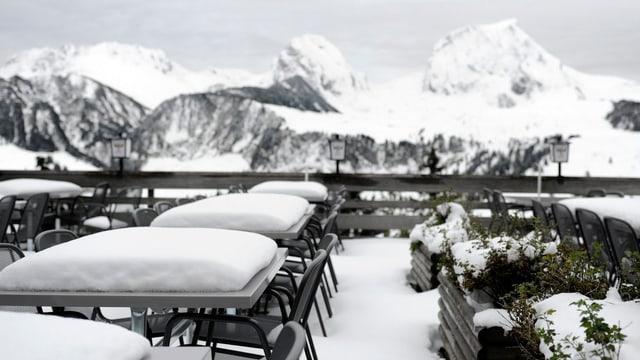 Blick über verschneite Restauranttische auf die Gantrisch-Bergkette.