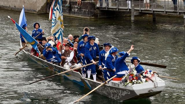 Ein Pontonierboot beladen mit blau-uniformierten Personen und Fahnen an Bord.