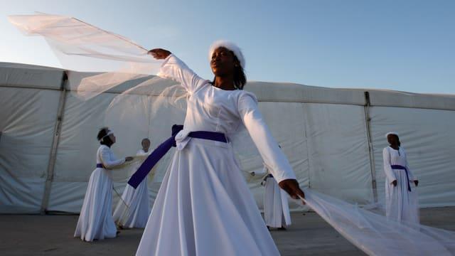 Eine Frau im weissen Gewand tanzt.