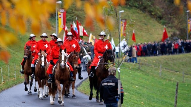 Ein Umzug von Sattel Dorf, angeführt von den Roten Schwyzern zu Pferde (Archivbild).