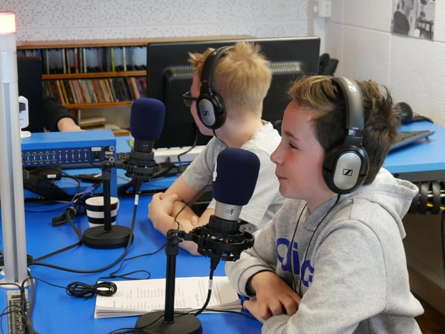 Kinder vor Mikrofonen