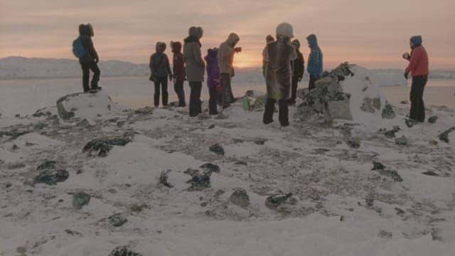 Es ist Winter. Eine Gruppe von Menschen wärmt sich mit heissen Getränken.