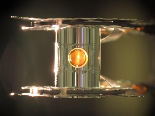 Kleiner Metallblock mit gelbem Fensterchen.
