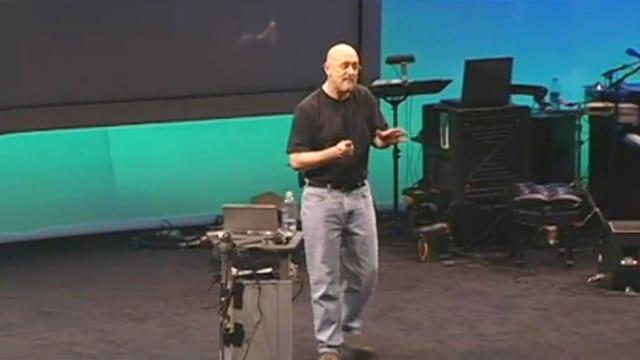 Ein Mann mit Jeans und T-Shirt hält einen Vortrag.