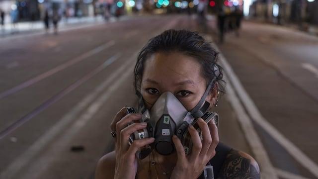 Junge Frau mit Gasmaske auf nächtlicher Hongkonger Strasse.