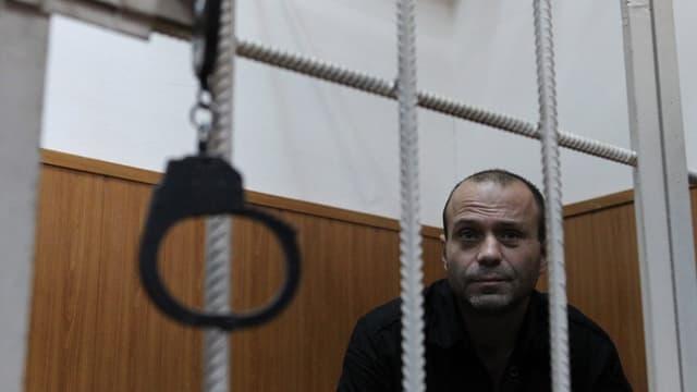 Mann hinter Gittern im Gerichtssaal.