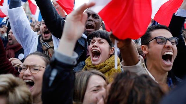 Eine gruppe junger Demonstranten schreit in die Menge.