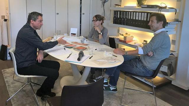 Drei Personen diskutieren an einem Tisch.