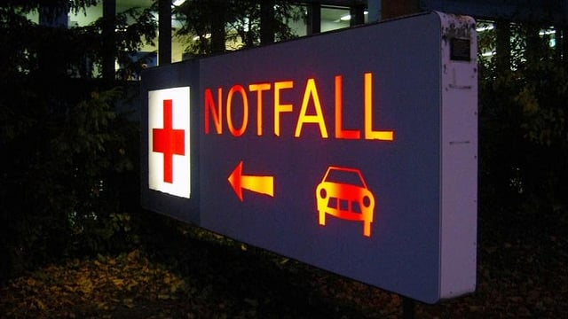 Das beleuchtete Schild, das zum Notfall weist