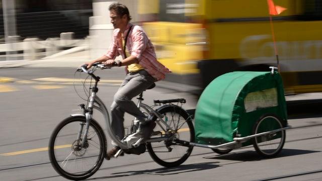 Mann fährt ein Elektrobike mit einem Kinderanhänger.