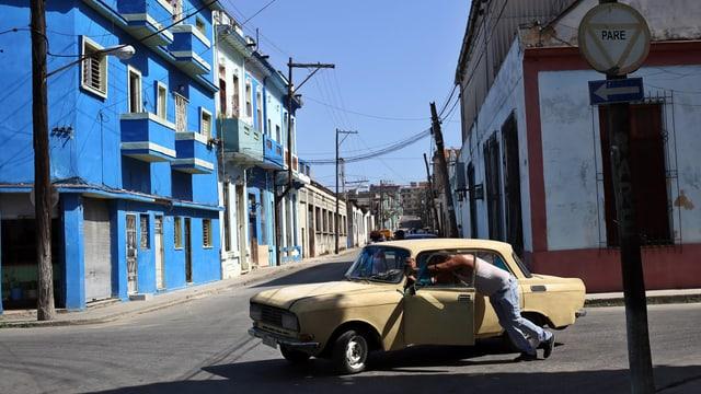 Mann schiebt Auto vor einer neu gestrichenen, blauen Fassade.