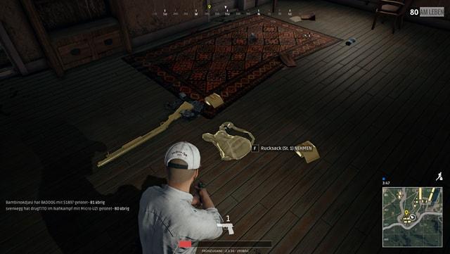 Rucksack und Schrotflinte liegen auf dem Boden dieses Hauses.