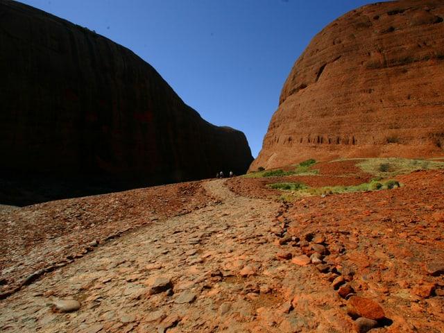 Bergige Landschaft in Australien - die Erde ist rötlich und die Gegend karg.