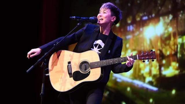 Eine Frau mit Gitarre auf einer Bühne.