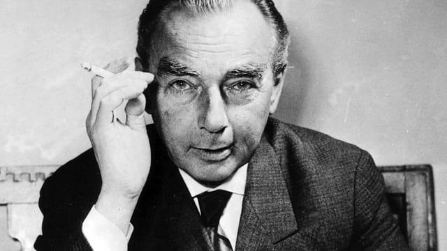 Erich Kästner in einem grauen Anzug mit Zigarette in der Hand.