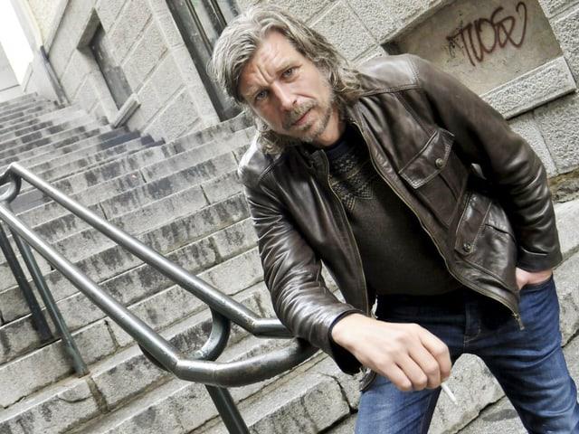 Karl Ove Knausgård auf einer Treppe. Er hat eine Zigarette in der Hand und lehnt an ein Geländer.
