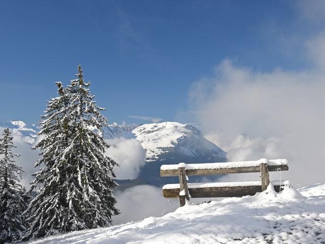 Verschneite Bank auf einem Berg - Voralpen - der Himmel wird klar die sonne kommt hervor.