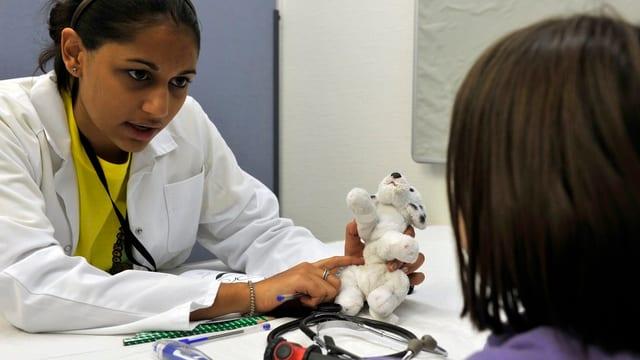 Kinderärztin spricht mit Kind und hält ein Stofftier in der Hand