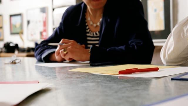 Frau sitzt am Arbeitstisch, Gesicht ist nicht sichtbar.