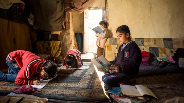 Kinder lernen in einem Raum in verschiendenen Bücher