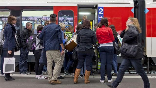 Passagiers avant la porta d'in tren da la SBB