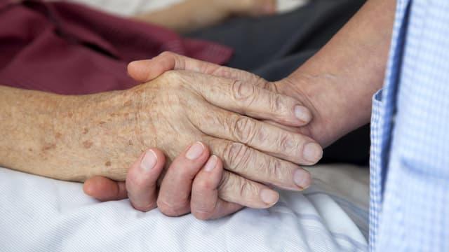 Eine Pflegende hält einem älteren Mann auf einem Bett die Hand.