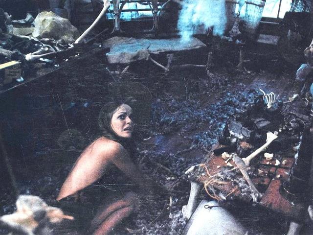 Eine junge Frau kriecht auf einem dreckigen Boden.