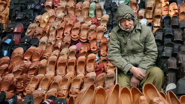 Junge verkauft Schuhe am Strassenrand.
