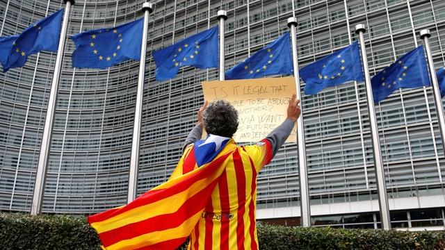 Mann mit EU-Flagge als Mantel vor dem EU-Gebäude mit EU-Fahnen.