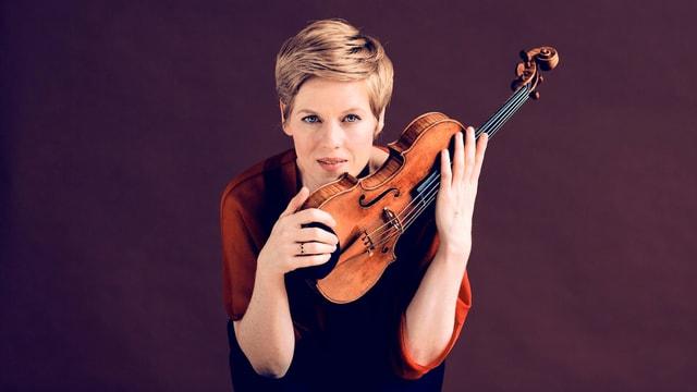 Eine junge Frau mit kurzem Haar hält eine Violine in den Händen.