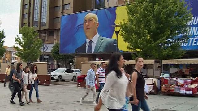 Strassenszene in Kosovo mit einem riesigen Wahlplakat.