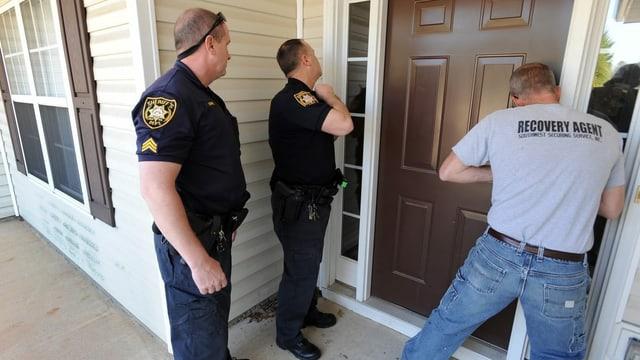 Polizisten lassen eine Tür für eine Zwangsräumung aufsperren.