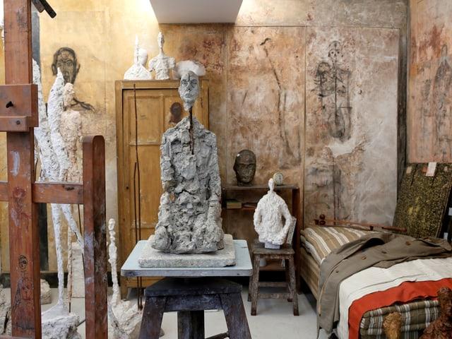 Ein Raum voller Skulpturen mit einem Schrank und einem Bett.