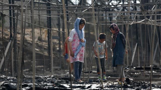 Kinder stehen zwischen dem verkohlten Gestänge der abgebrannten Zelte.